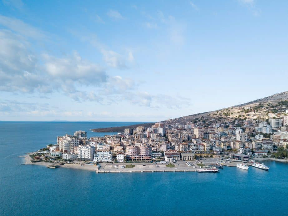 Photo of the Saranda port which has beautiful bright blue water and lots of buildings on land. Albania travel restrictions: Travelling Albania in 2021