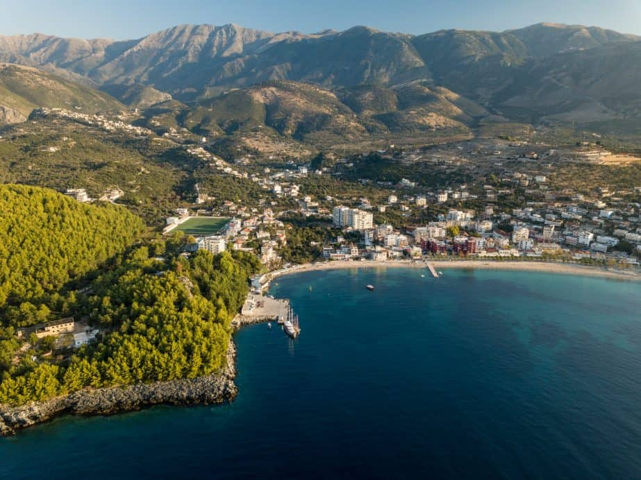 Drone photo of the town of Himare which has a mountain and the sea beanth it. Beautiful bright green and blues. Albania travel restrictions: Travelling Albania in 2021